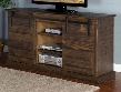 "Homestead Collection 3577TL 65"" TV Console with Sliding Farm Door Hand Sawn Weathered Distressing and Adjustable Shelves in Tobacco Leaf"